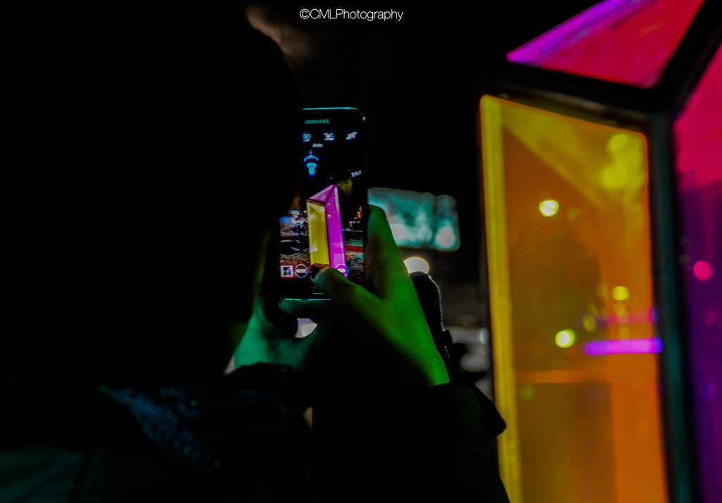 February 17 2017, a Calgary citizen takes a photo on her cell phone of a light prism during the Glow Festival Down Town.